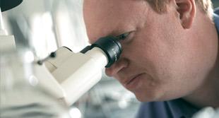 man looking in miscroscope
